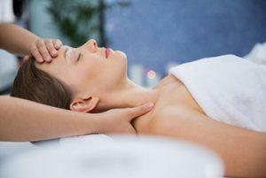 Portrait de profil d'une femme sur le dos, les yeux clos, recevant un massage de la tête et des épaules