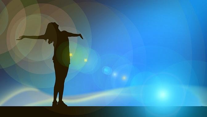 Femme recevant les rayons du soleil sur un fond de ciel bleu